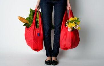 Женщина несет тяжелые сумки