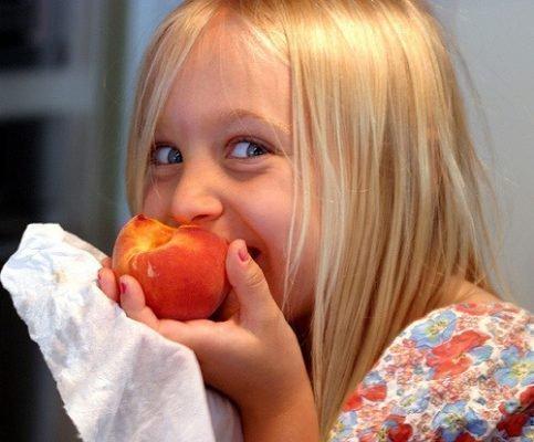 Ребенок ест персик